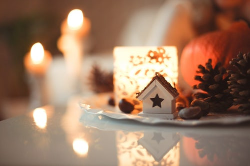 Small house with cut-out star shape, pine cones and candle table decoration
