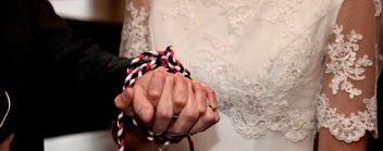 Bride and groom holding hands which are bound with a handfasting cord