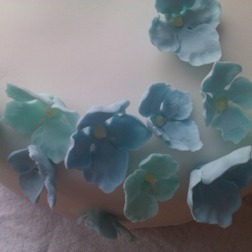 White cake decorated with blue sugar paste flowers