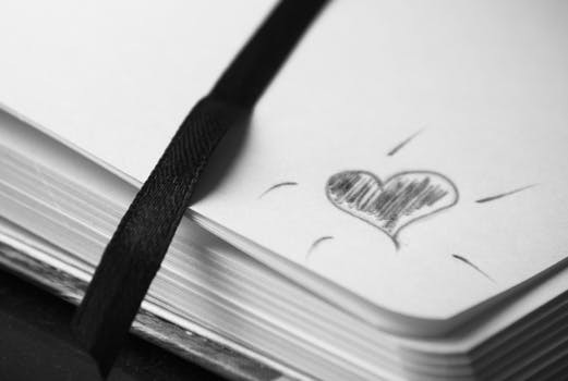 doodle of a heart in black pencil in the corner of the page in a notebook