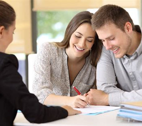 Couple signing loan documents with their eyes closed.