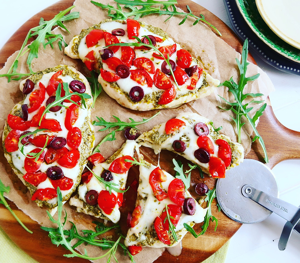 Chicken based pizza with pesto, tomatoes, and olives