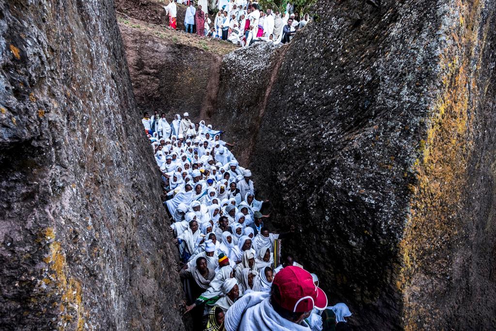 דרך נקיק צר בסלע צועדים בצפיפות ההמונים אל הטקס לכבוד השנה האזרחית החדשה  בעיר לליבלה   שבאתיופיה