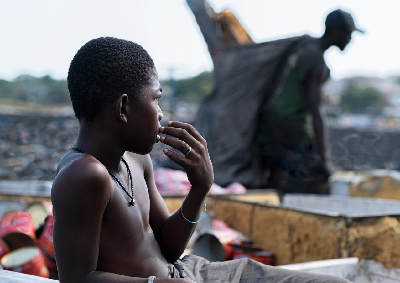 מנוחה בין שקי פסולת אלקטרונית בגאנה