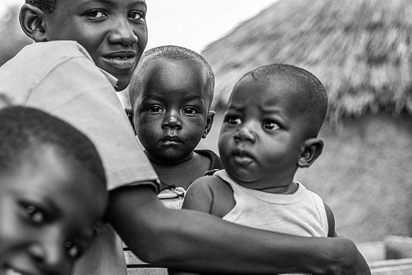 הם ישבו בעגלת עץ גדולה צופים בריקודים שנערכו ברחבת הכפר בגאנה