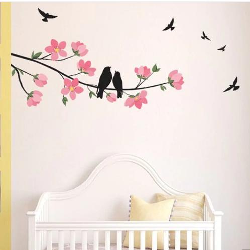 ציפורים שחורות על ענף עם פרחים וורודים