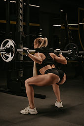 photo-from-fit-woman-with-blonde-hair-who-is-squatting-with-barbell-near-squat-rack-gym.jp