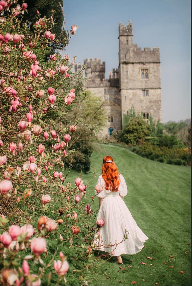 Girl in dress walking toward Irish castle with flower tree to side