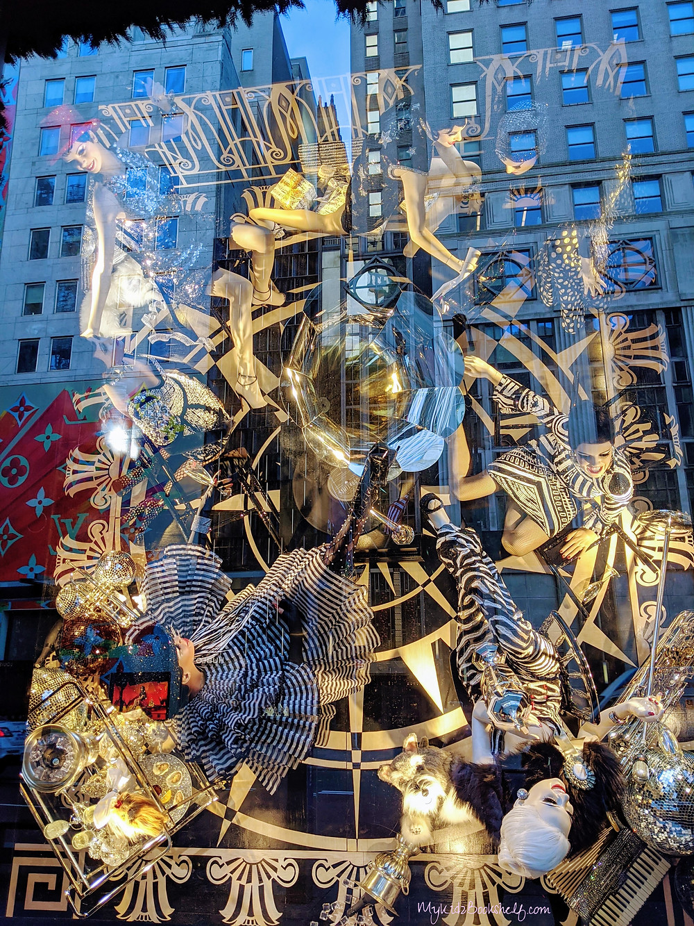 window-display-in-bergdorf-goodmans-in-nyc-showing people-sitting-around-a-gramophone-laughing-and-talking