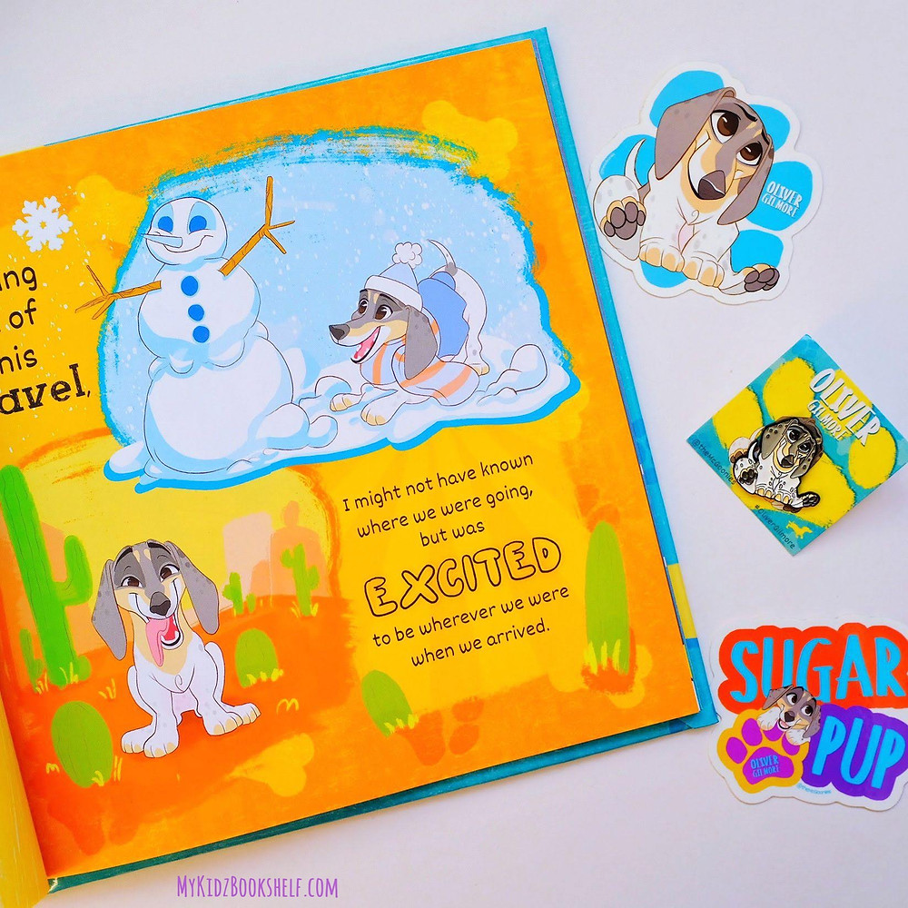 Page from book Oliver Gilmore shows dachshund playing in the snow with stickers and pins on side of book