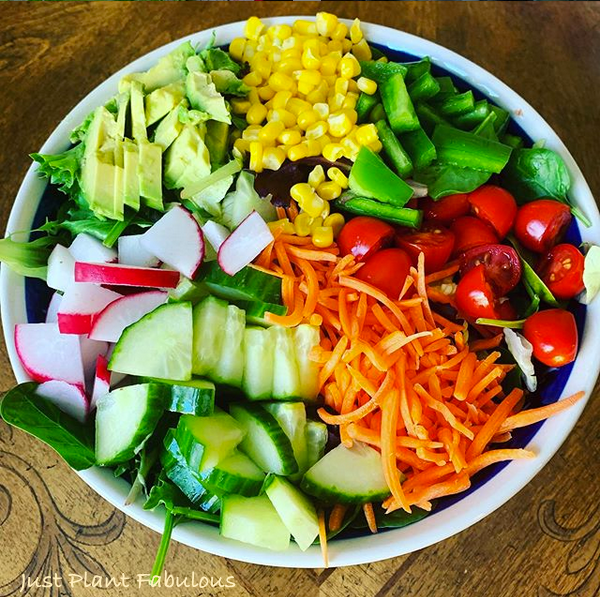 colorful fresh vegetables in a bowl- corn, radish, cakes, avocado, tomatoes and carrots