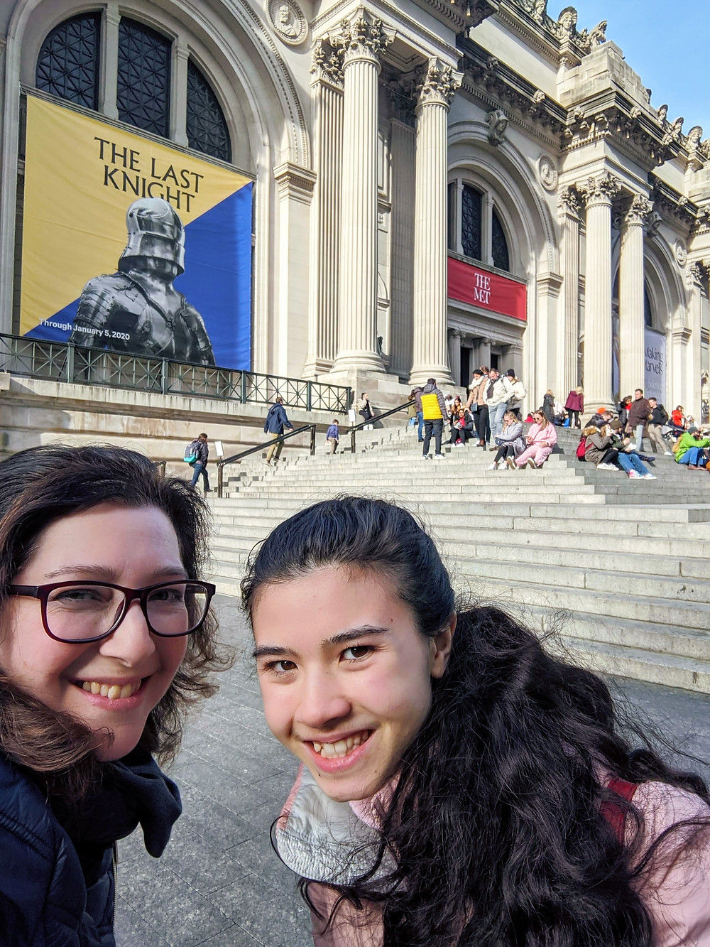 woman-with-glasses-and-teen-girl-pause-outside-of-The-Metropolitan-Museum-of-Art-in-background