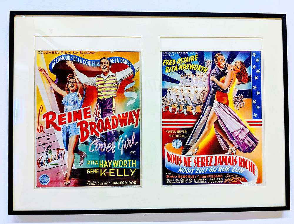 framed movie posters with Rita Hawyorth and Gene Kelly and Fred Astaire. they are dancing wearing very colorful costumes