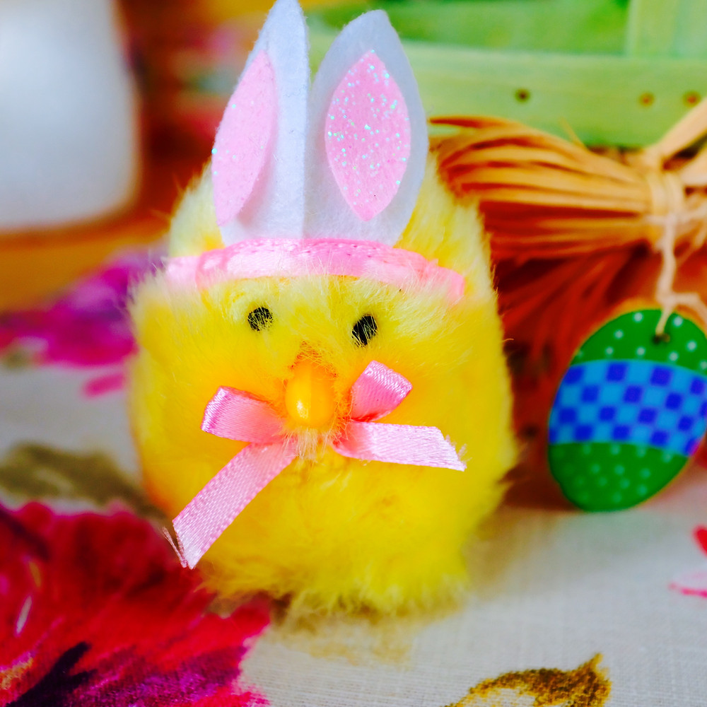fuzzy yellow chick with bunny ears surrounded by easter decor