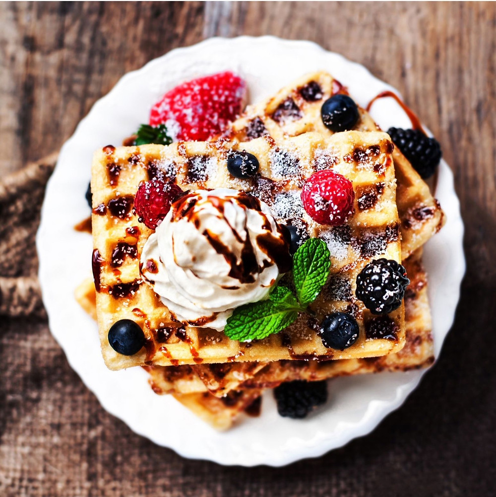 Belgian-waffles-with-vanilla-ice-cream-in-between-strawberries-whip-cream-and-chocolate-syrup-on-top
