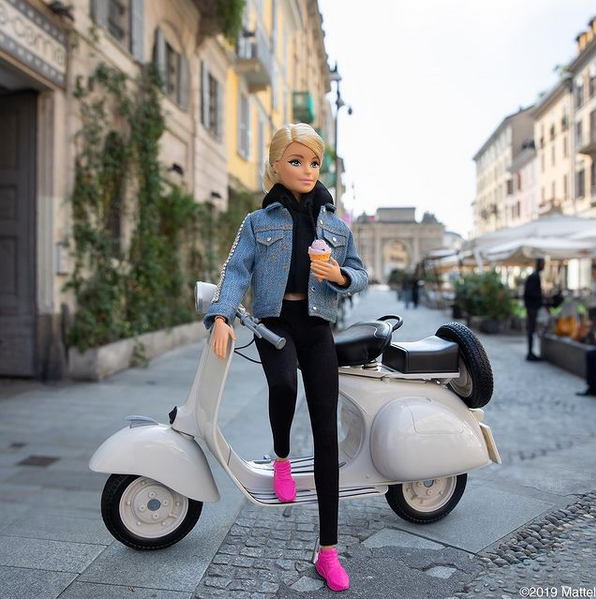 Barbie with jean jacket sitting on Vespa scooter with gelato on city street