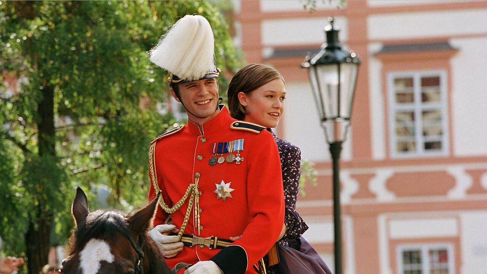scene from movie, The Prince and Me with Julia Styles riding on the horse with a prince in royal attire