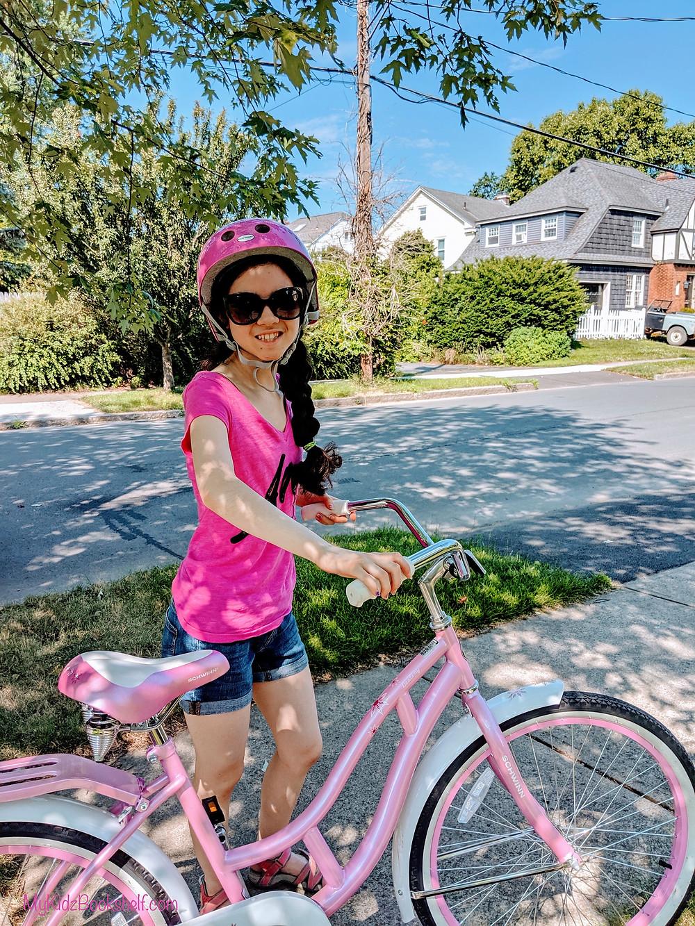 girl wearing bike helmet holding onto handlebars of cruiser bike standing on sidewalk in treelined neighborhood
