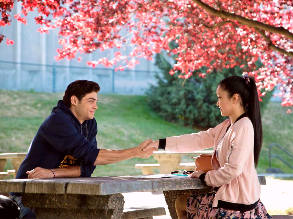 scene from To All the Boys I've Loved Before with Lara Jean and Peter sitting at a picnic table
