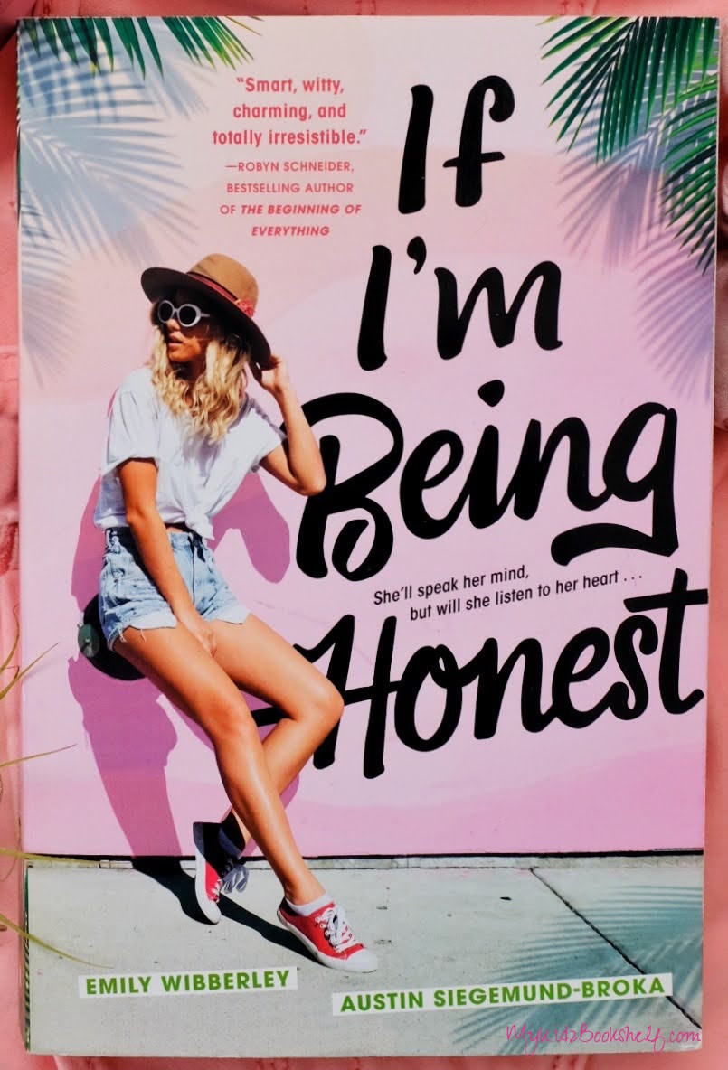 Girl with hat leaning against wall wearing shorts and sunglasses. Palm tree leaves on side. Book cover for If I'm Being Honest