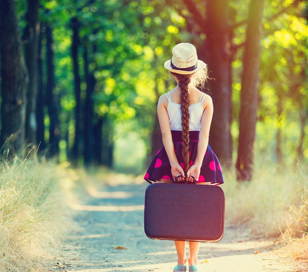 girl wearing hat holding suitcase standing on country road
