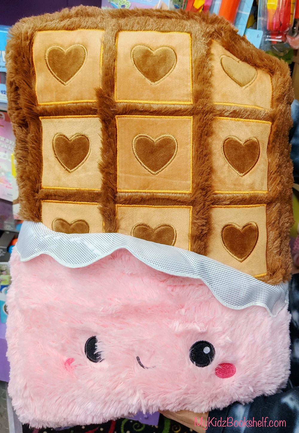 Squishable pillow in the shape of a large chocolate bar with a smiling face