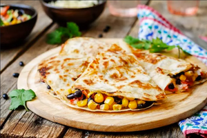 black bean and corn quesadillas on wooden table with colorful napkin