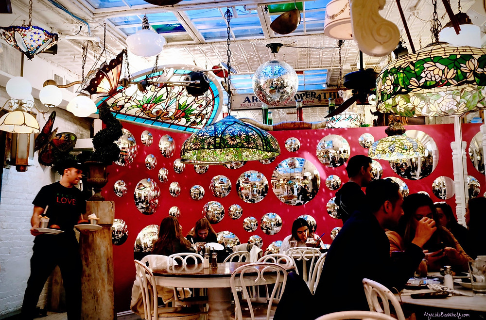 a-look-inside-Serendipity-3-cafe-with-tables-Tiffany-style-lamps-bubble-mirrors-a-waiter-serving-and-people-eating
