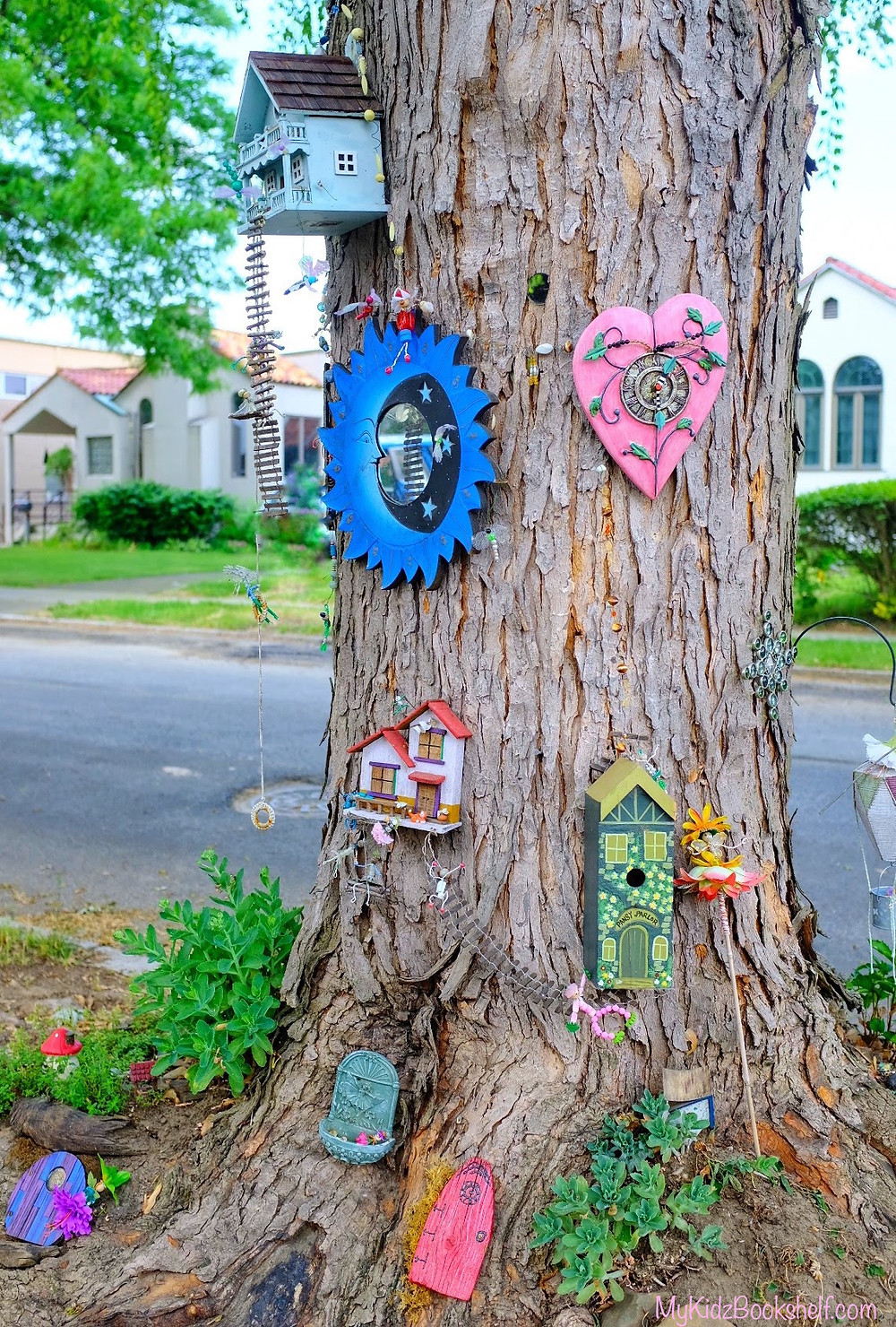 tree with fairy garden houses and fairy doors, mirrors and succulents