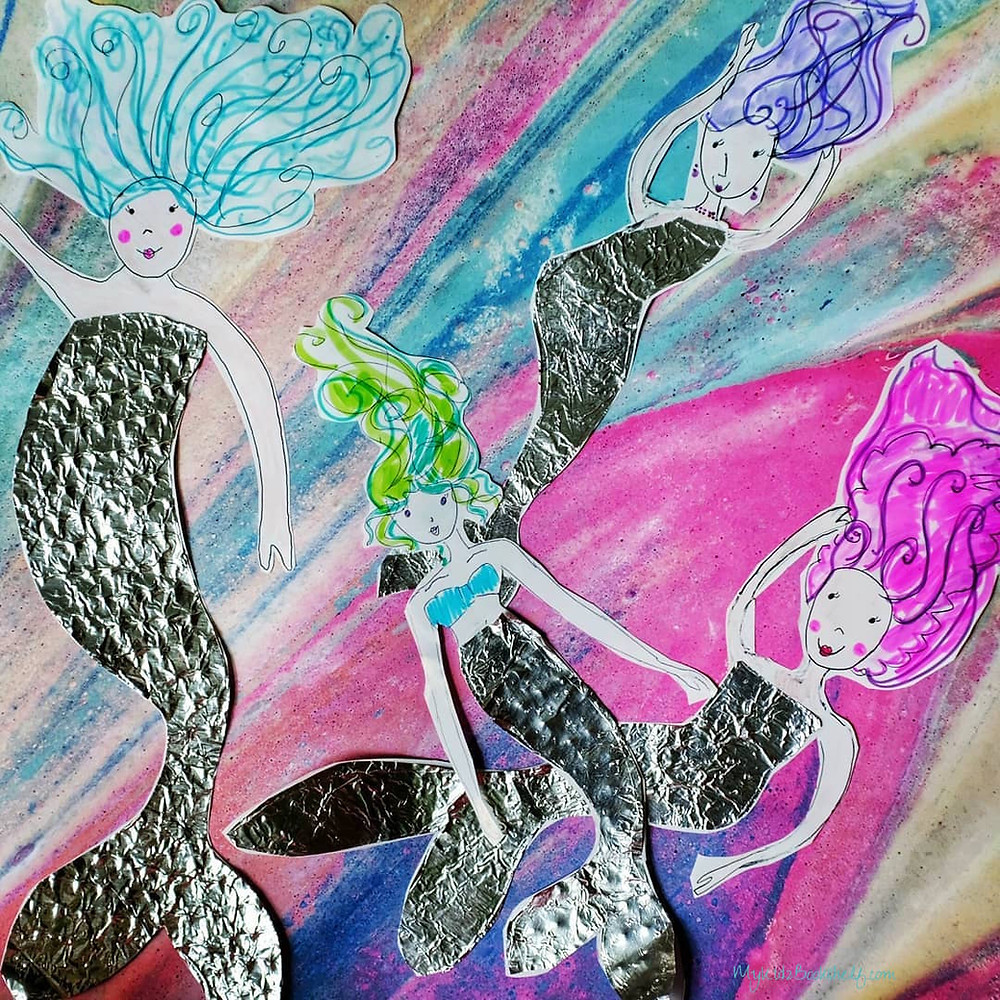 Mermaids-on-scrapbook-paper with colorful hair and tin foil tails