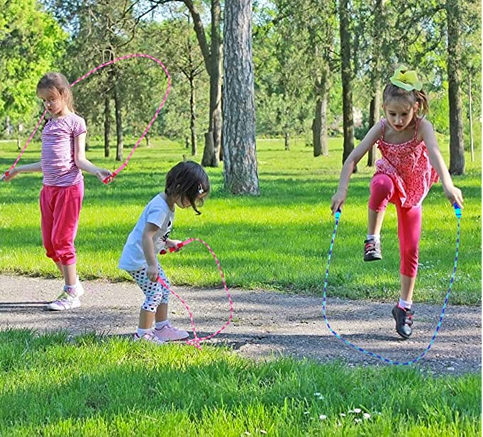 kids jumping rope on a walkway in a park.