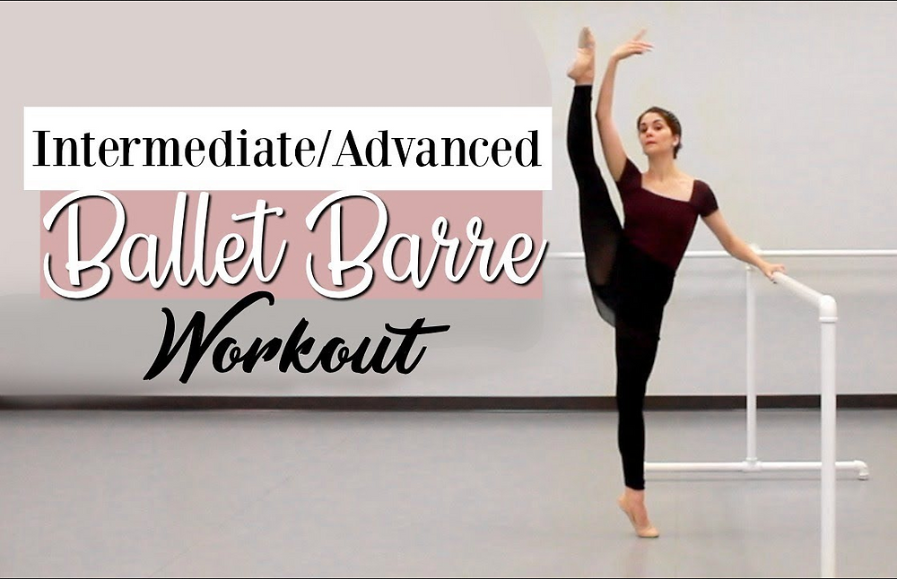 picture of ballet dancer Kathryn Morgan holding onto ballet barre with one arm overhead and leg stretched high