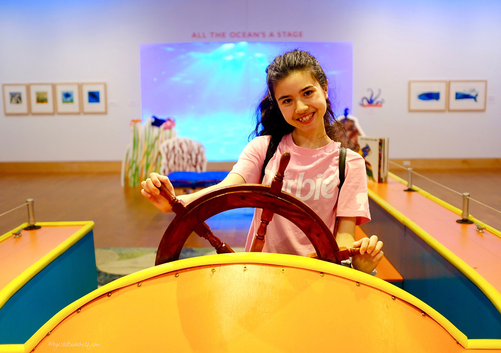 Cenzia from My Kidz Bookshelf posing behind boat wheel at The Eric Carle Museum of Picture Book Art