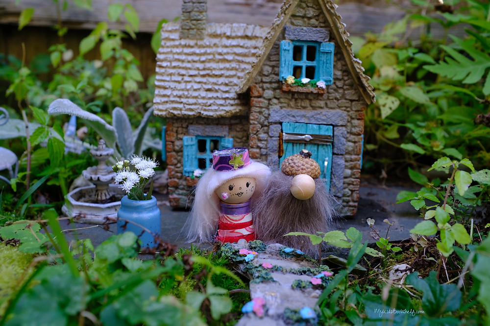 Fairy garden with cottage, fountain gnomes, flowers and pathway