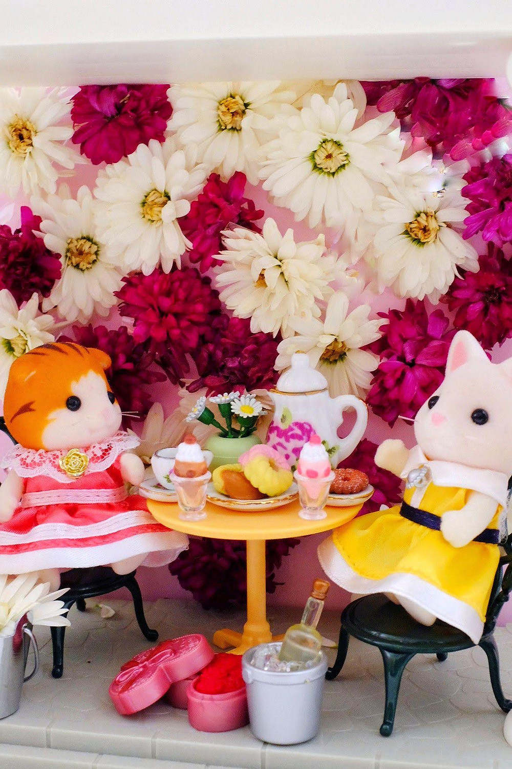 flower wall with Calico Critters Sylvanian Families sitting and having a tea party in front of flower wall