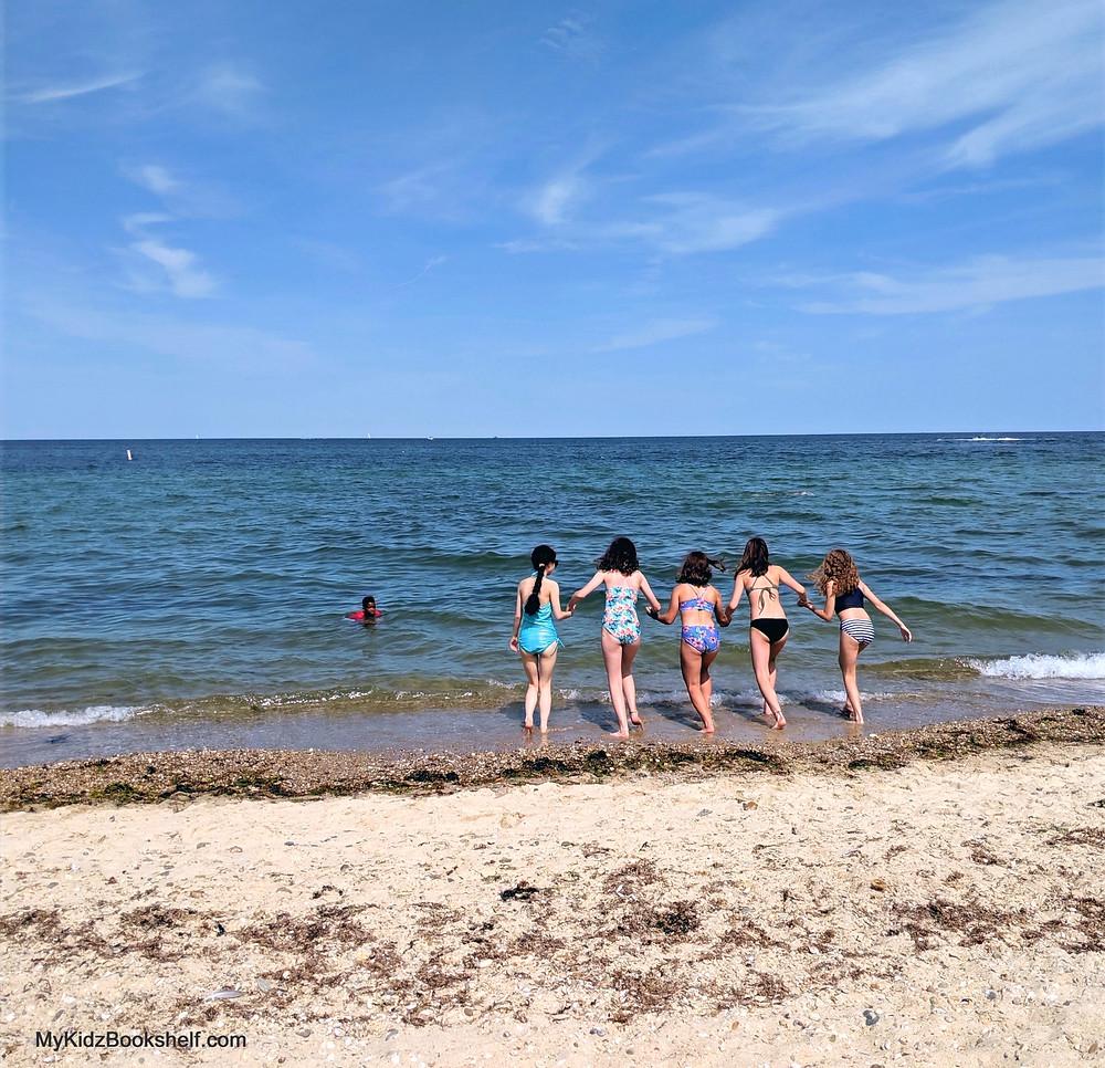girls running into the ocean holding hands