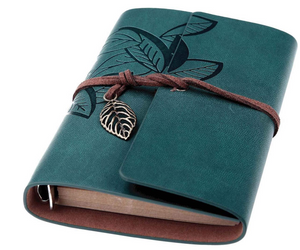 Leather bound journal with leaf imprint and wrapped with cord that has a leaf charm attached