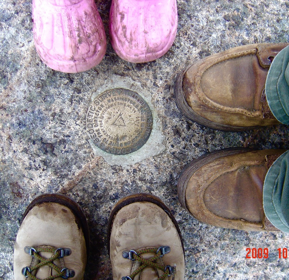 hiking-boots-around-metal-geodetic-mountain-survey