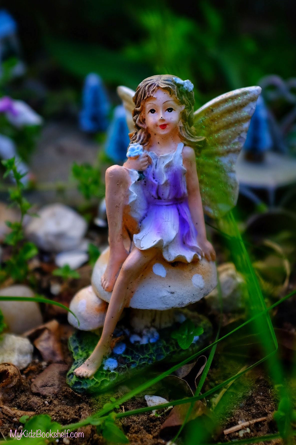 Fairy garden statue fairy with wings sitting on a mushroom