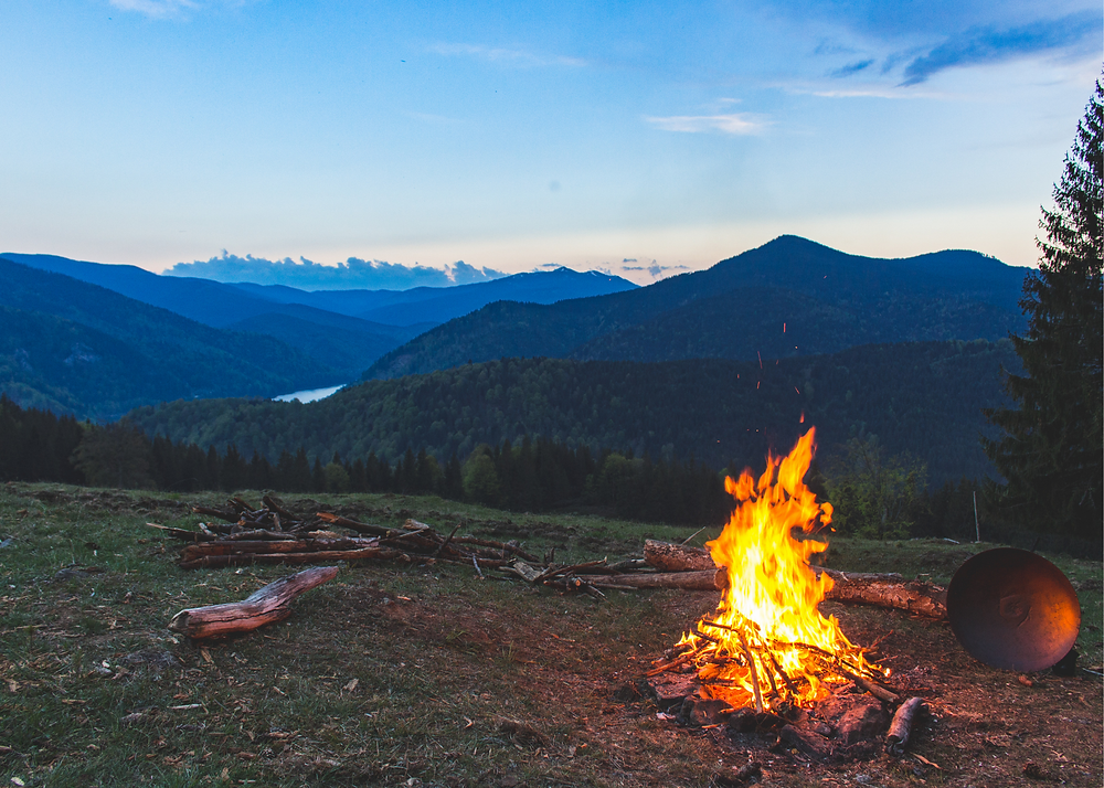 campfire at dusk with mountains in the background