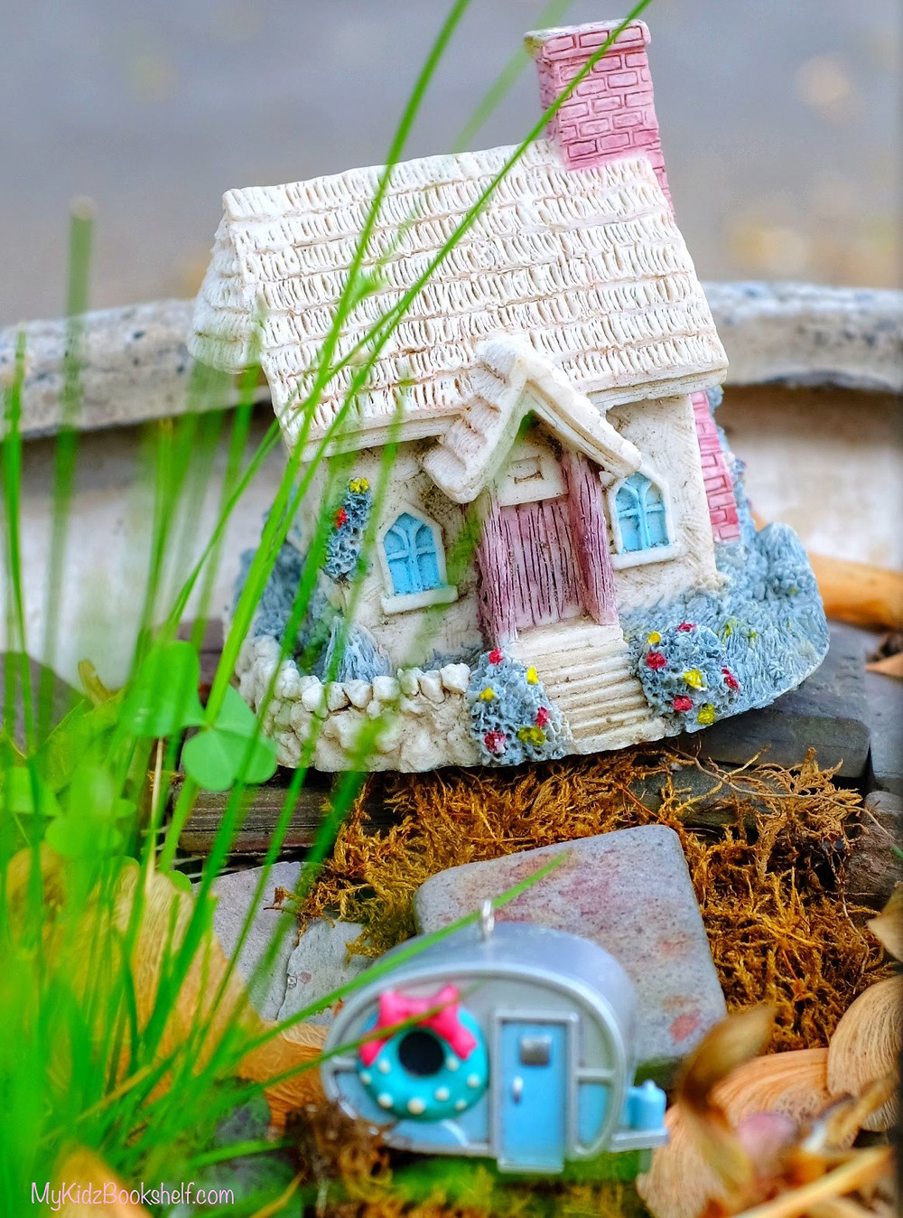 Fairy garden cottage with little old fashioned camper in moss, rocks, grass