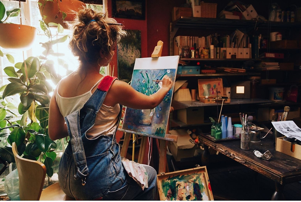 woman painting on a canvas in a studio with art supplies all around her