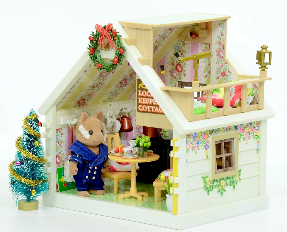 Sylvanian Families Lockkeeper cottage with figure standing by opening with decorated mini bottlebrush Christmas tree and wreath decorating house peak