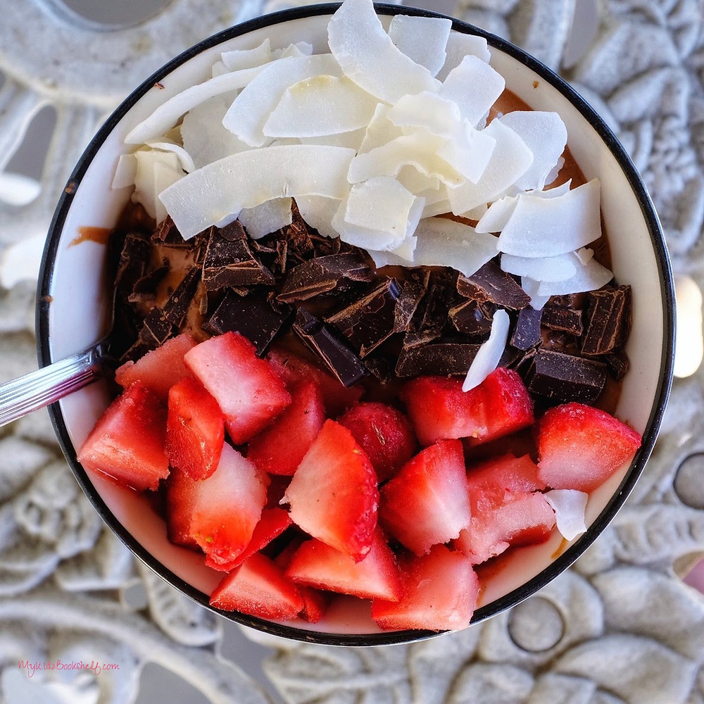 strawberries, chocolate, coconut in a smoothie bowl on a table