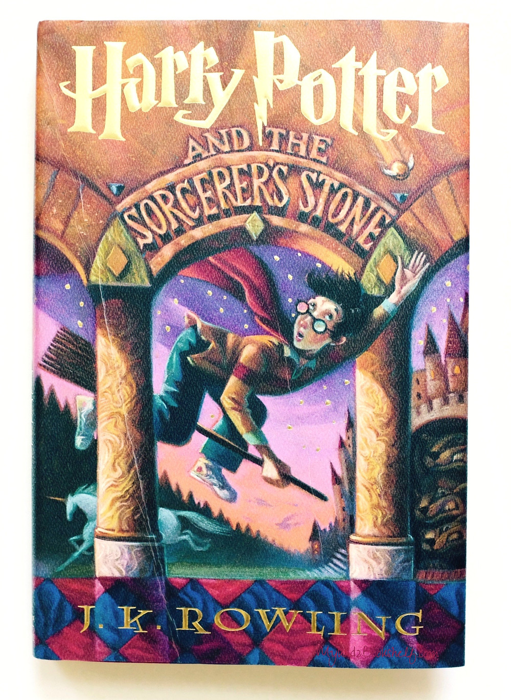 Harry Potter and the Sorcerer's Stone book cover by J.K. Rowling with Harry on broom flying through archway