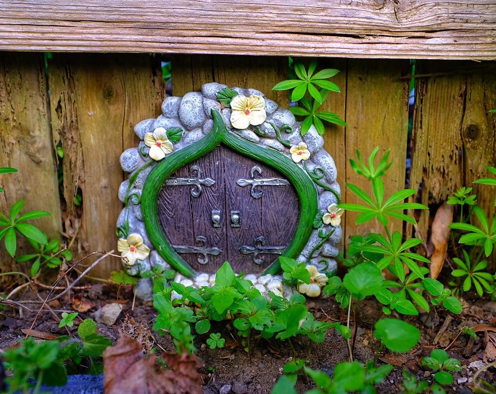 Fairy Garden door in garden by a fence with greenery