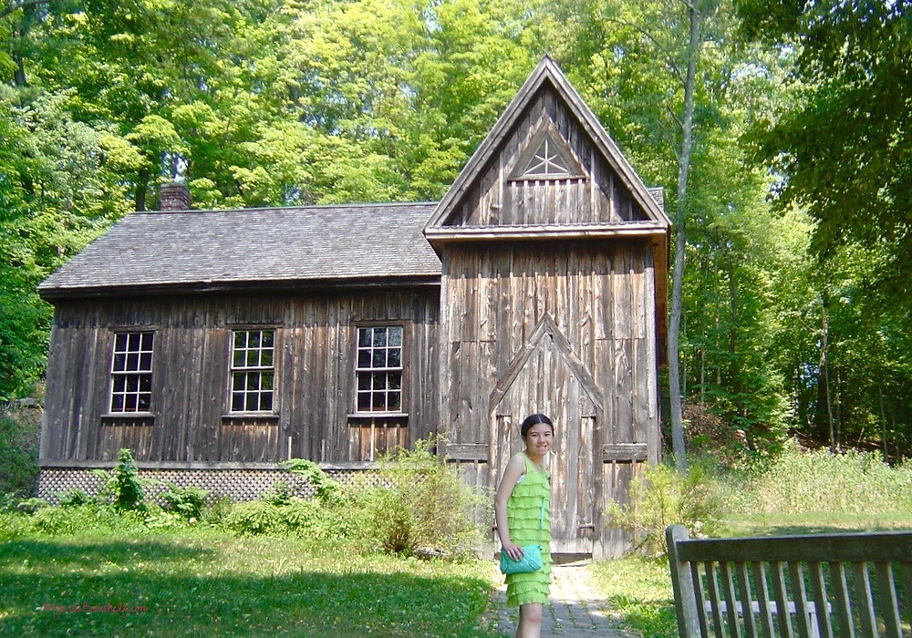 girl-standing-in-front-of-barn-by-Louisa-May-Alcott's-Orchard-House