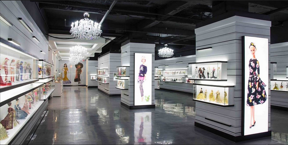 inside picture of Barbie Expo in Montreal with Barbie doll collectibles lining the walls and life sized Barbie murals on end caps of displays lit by hanging chandeliers