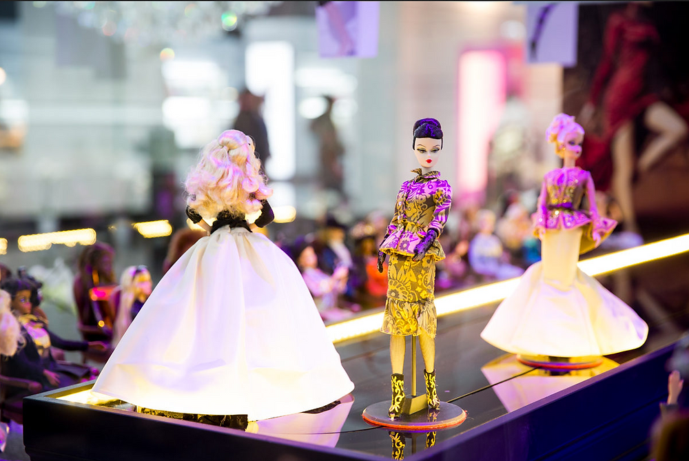 Different Barbie Dolls posed on a doll-sized catwalk on display at the Barbie Expo in Montreal