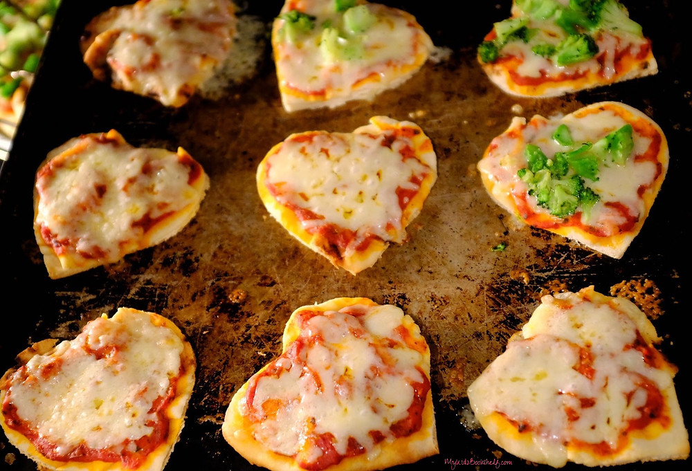 Heart shaped pizzas on a baking sheet in the oven